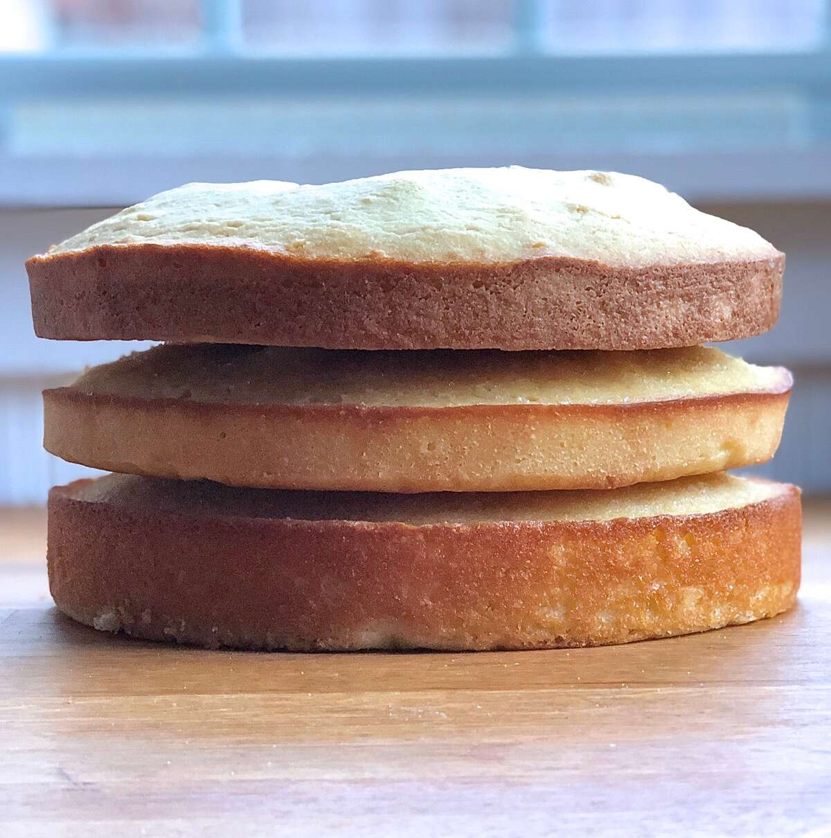 Three cake layers baked with three different sweeteners, stacked atop one another to show difference in rise