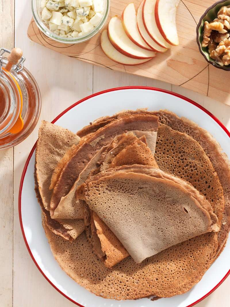 A plate of folded teff crepes, about to be enjoyed