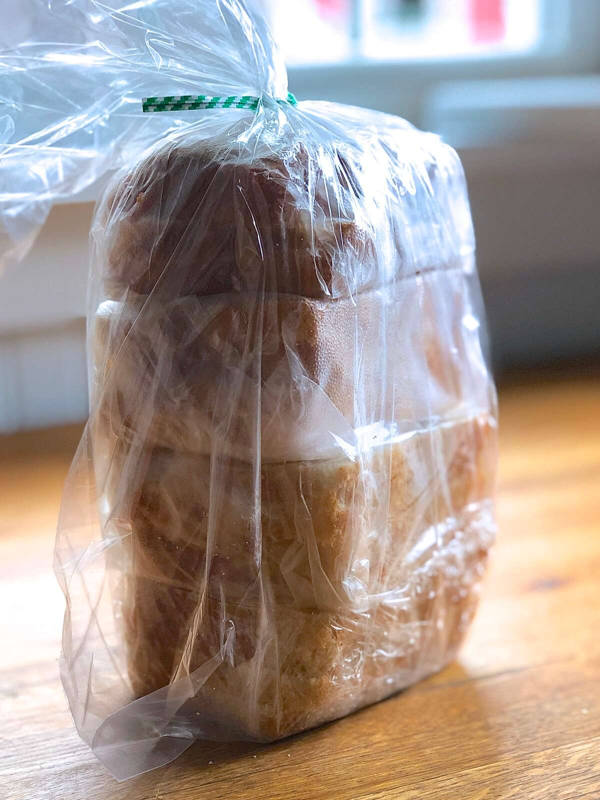 Individual packets of sandwich bread stored in a plastic bag, ready for the freezer.