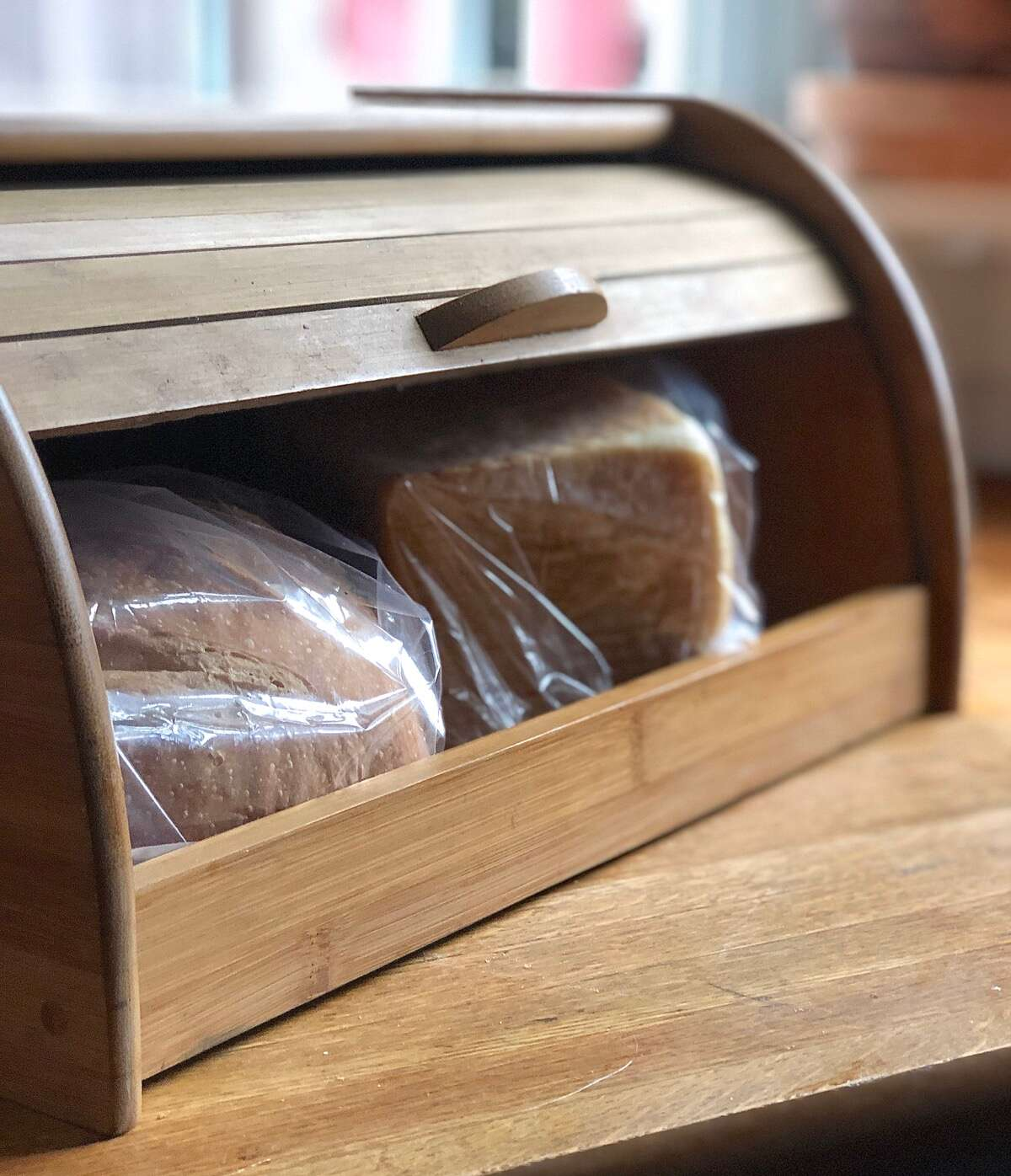 Two loaves of bread stored in a lidded wooden bread box.