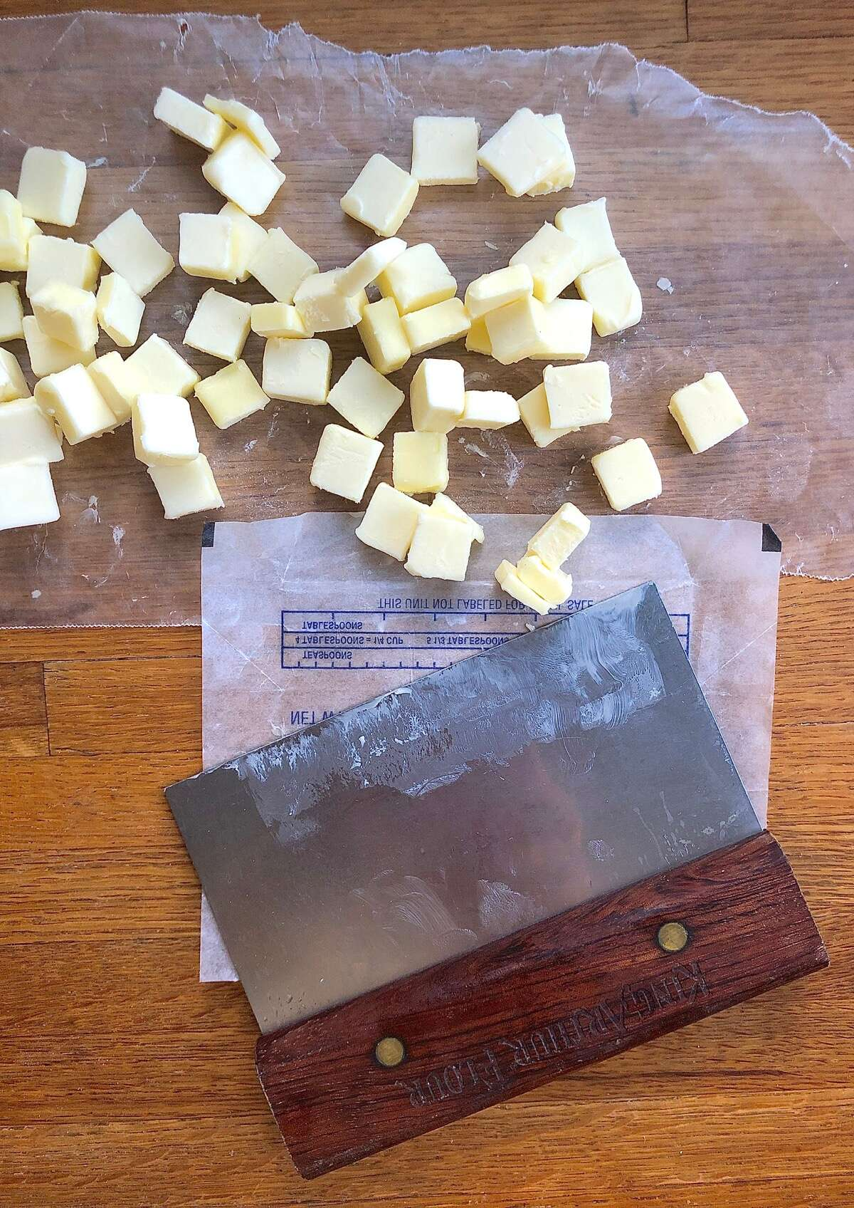 "Pile of 1/2"" butter cubes with bench knife"