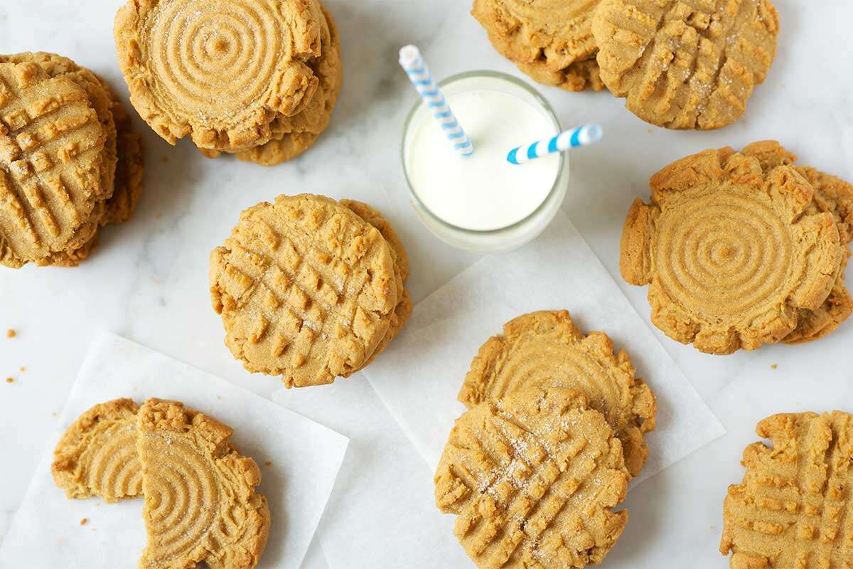 Stacks of peanut butter cookies on a table next to a glass of milk