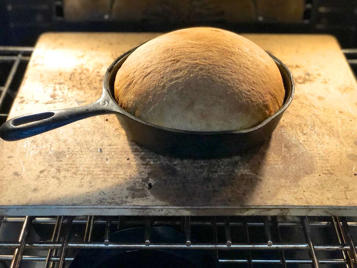 Sourdough bread baking in a cast iron skillet in the oven.