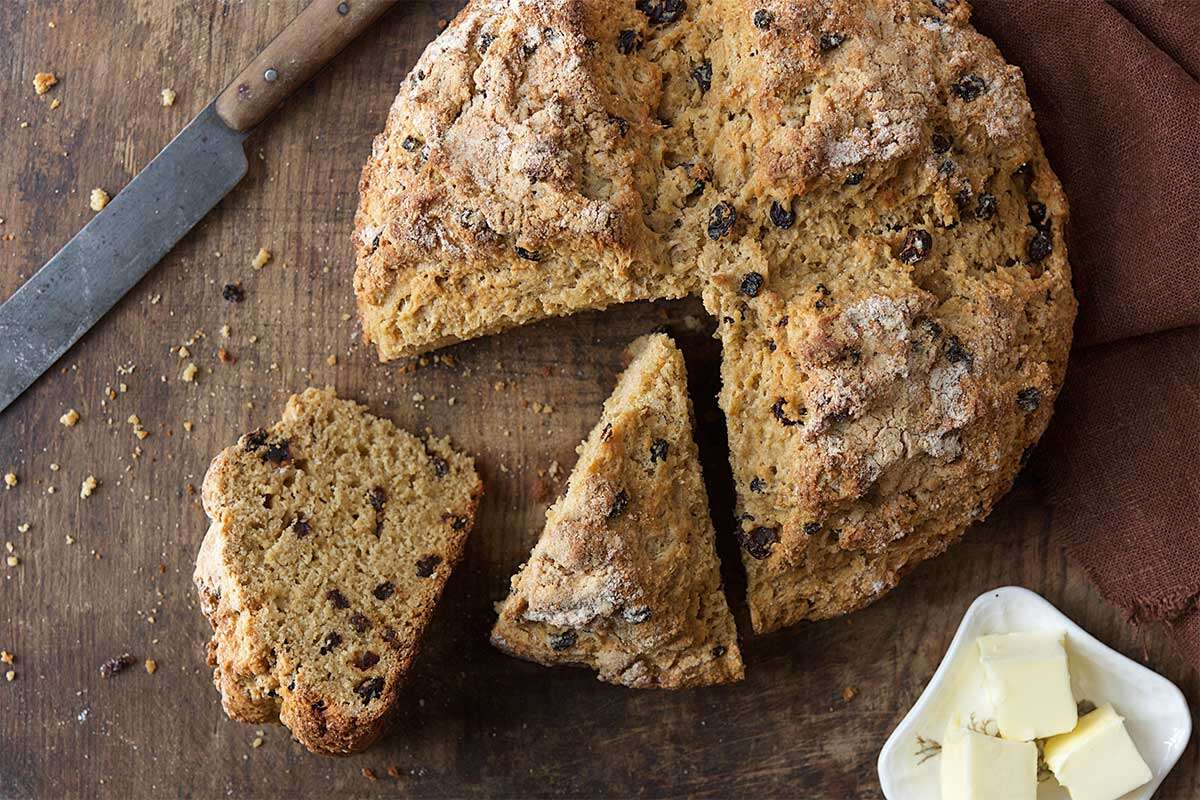 A loaf of Irish soda bread with a wedge cut out of it
