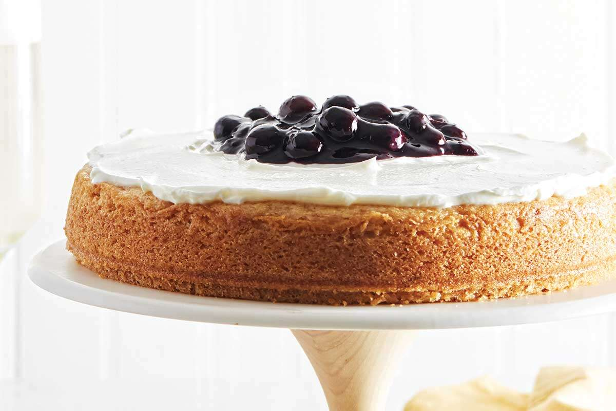 A lemon tendercake topped with blueberry compote on a cake stand