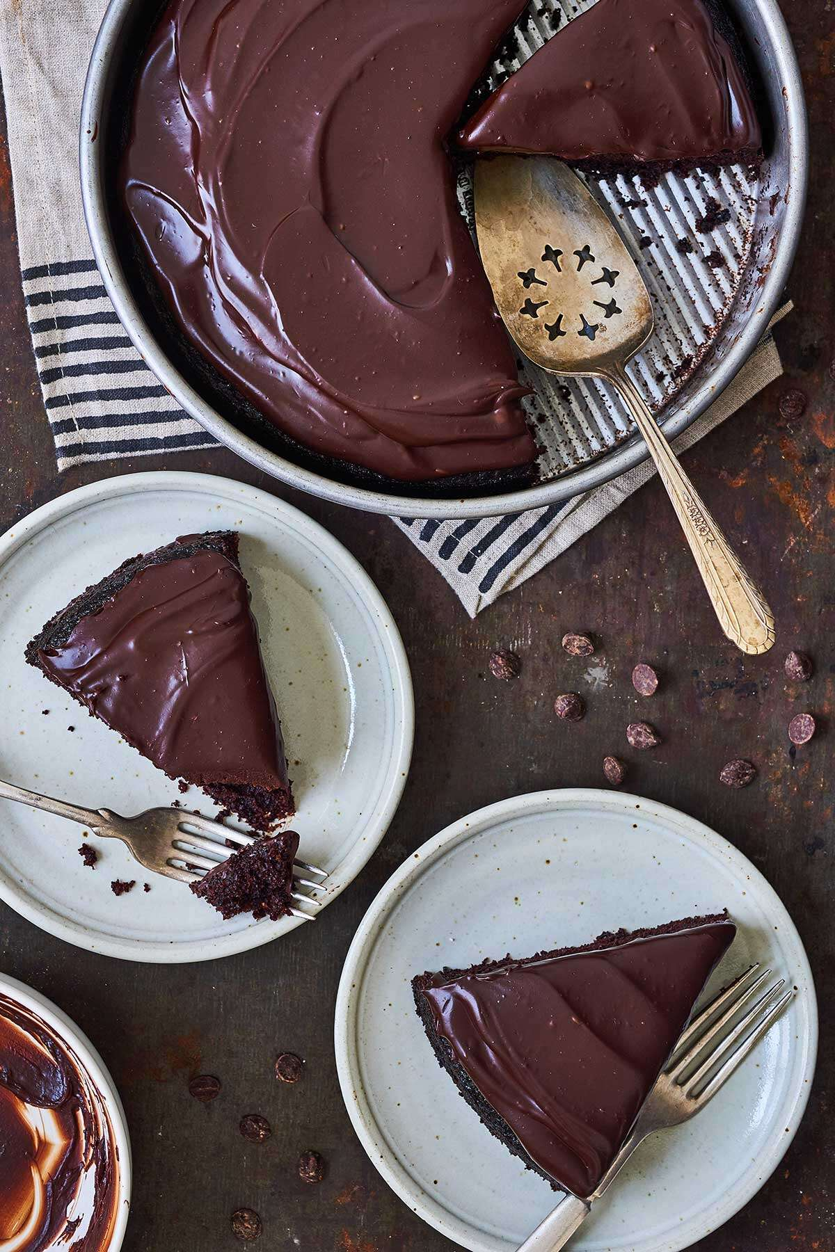 A round chocolate cake topped with chocolate frosting and a few slices on plates