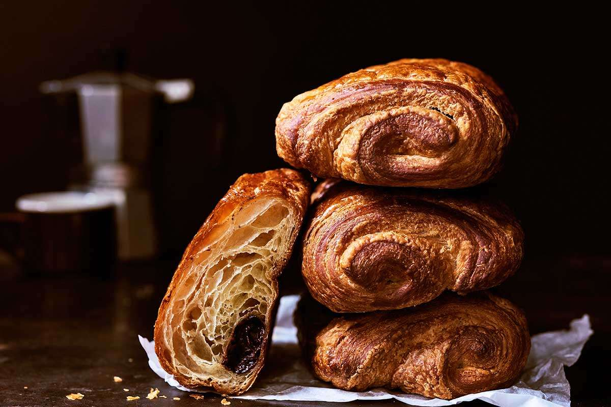 Stack of pain au chocolat, with one sliced in half to show its layers