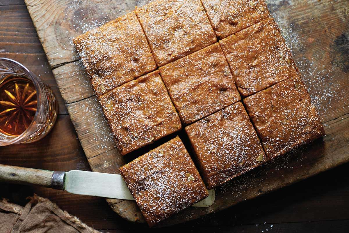 A pumpkin spice cake pan cake cut into slices and topped with confectioners' sugar