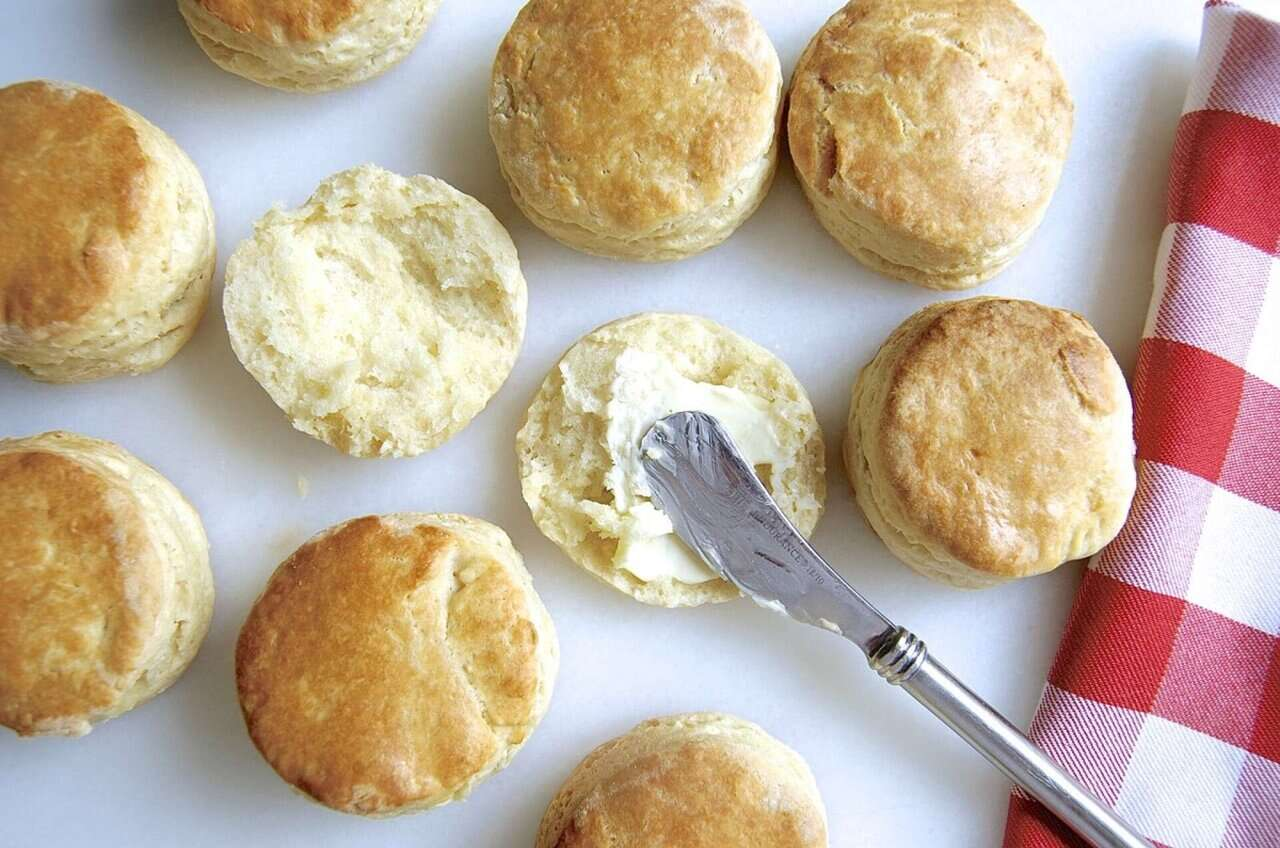 Biscuits on a baking sheet, with one split and buttered
