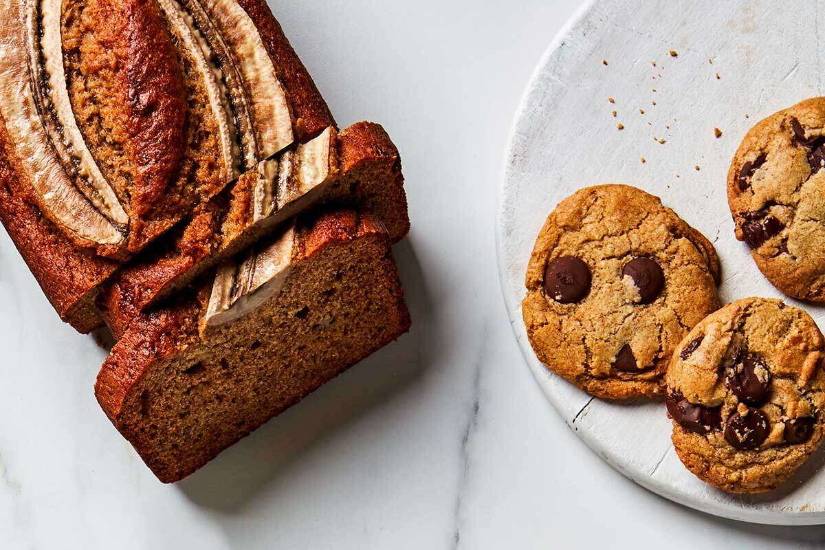 A loaf of rye banana bread cut into slices next to rye chocolate chip cookies