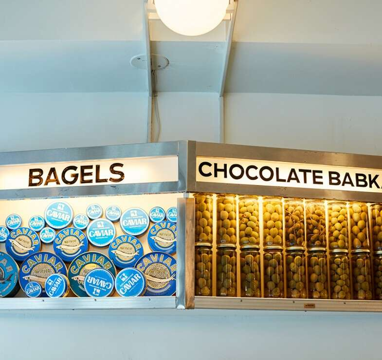 Russ and Daughters display case containing caviar tins and jars of olives