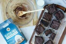 Gluten-free brownies with a box of gluten-free flour, a mixing bowl, and a glass of milk
