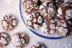 A platter of chocolate crinkles next to a few scattered cookies on a table