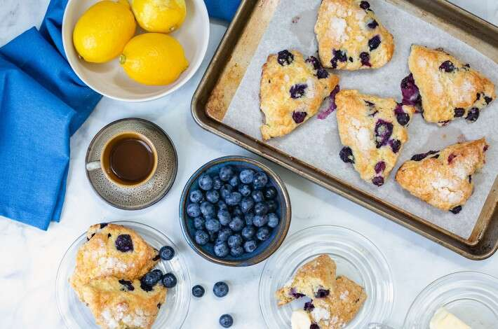 Fresh blueberry scones on a baking sheet next to a bowl of blueberries, a few lemons, a coffee, and butter.