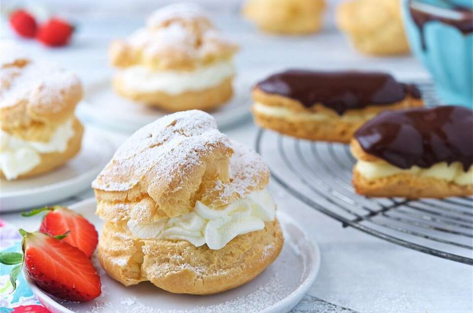 Cream puffs filled with pastry cream and eclairs topped with chocolate