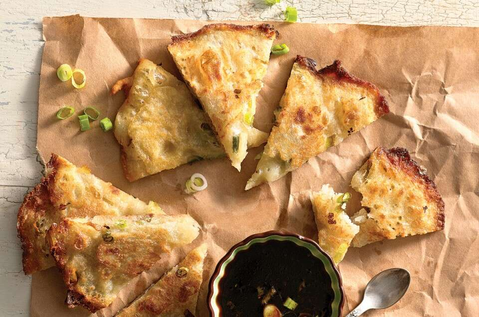 Scallion pancakes cut into wedges with a side of dipping sauce