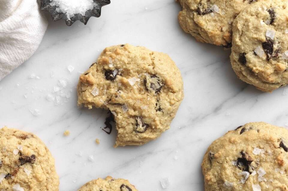 Gluten-Free Almond Flour Chocolate Chip Cookies dusted with sea salt on a marble board