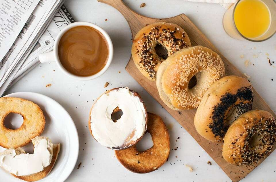 A bread board with homemade bagels next to a cup of coffee, orange juice, and a toasted bagel with cream cheese