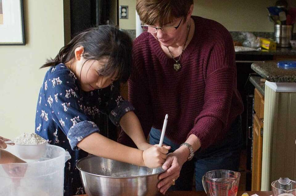 A mother and a daughter baking together happily