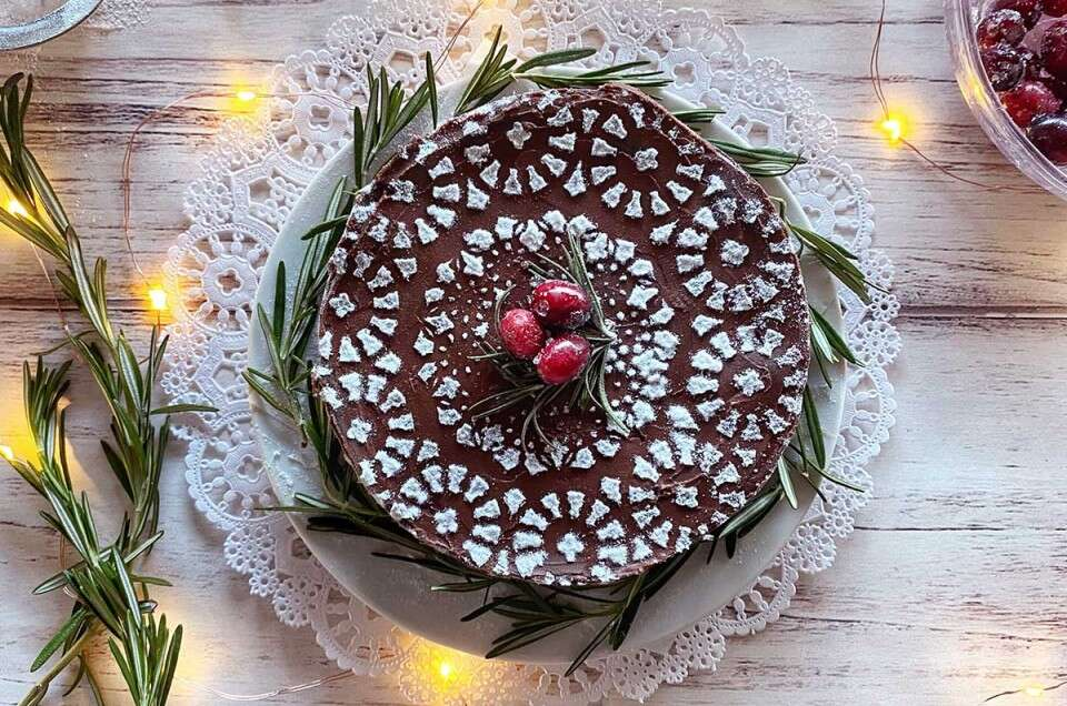 A flourless chocolate cake stenciled with confectioners' sugar, cranberries, and twinkling lights
