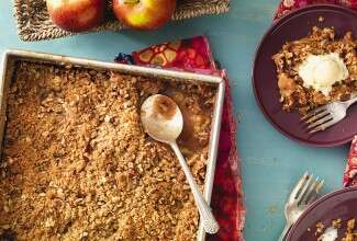 A pan of apple crisp on a table with a few apples and two plates of apple crisp with ice cream