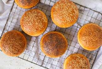 Homemade hamburger buns topped with seeds cooling on a rack