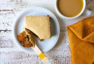 Square of apple cake with brown sugar frosting on a plate with a fork, coffee on the side.