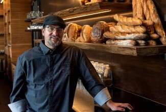 Chef John Kraus in front of shelves of baked goods