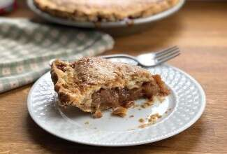 Slice of apple pie on a plate, flakes of crust scattered around slice.
