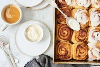 A tray of cinnamon buns with a bowl of frosting next to a cup of coffee