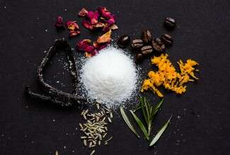 A pile of sugar with ingredients that can be infused into it to add flavor: vanilla bean, rose petals, coffee beans, orange zest, rosemary springs, and lavender flowers