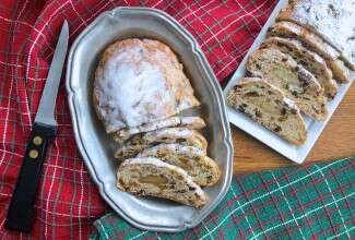 Two loaves of Christmas Stollen, sliced on plates on a table.