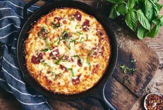 A Gluten-Free Pan Pizza in a cast iron pan on a wooden table garnished with fresh herbs