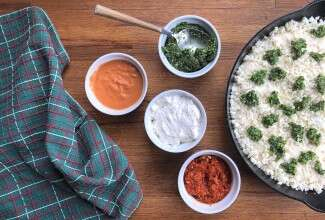 Pizza being topped with sauce, four bowls of sauce: pesto, romesco, white, and pink vodka.