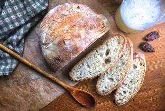 Naturally leavened sourdough bread made with yeast water in place of standard sourdough starter, sliced open and set on a wooden table.