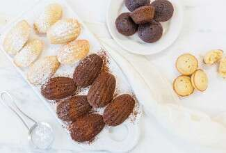 A platter of chocolate and vanilla madeleines shaped traditionally next to a few madelelines shaped like mini muffins
