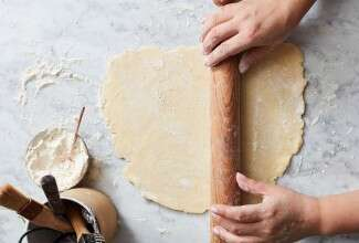 Hands rolling out pie crust