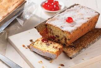 Sliced fruitcake topped with candied cherries
