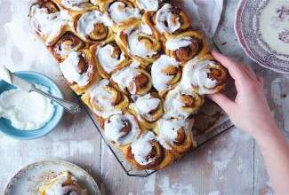 A batch of soft cinnamon rolls on a cooling rack with a hand reaching for a roll