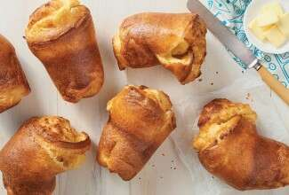A set of six baked popovers next to a ramekin of butter