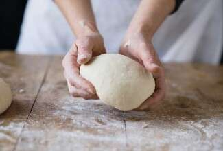 Hand holding bread dough