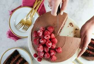 A chocolate mousse cake with raspberries being sliced