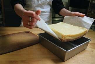 Hands lifting bars from pan with parchment paper