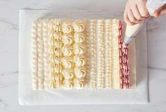 Hands piping designs on a sheet cake