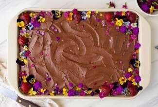 A sheet cake topped with chocolate frosting and edible flowers