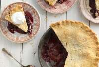A cherry pie made with a gluten-free crust with a few slices on plates, ready to be enjoyed