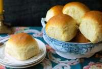 Golden soft dinner rolls in a bowl, one on a bread plate.