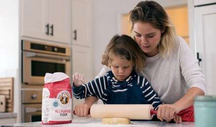A mother and son using a rolling pin to roll out cookie dough