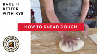 Hands kneading dough on a counter